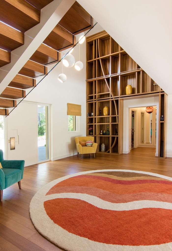 deco salon vintage des années 70 avec tapis rond coloré meuble bibliotheque de bois parquet bois murs blanc fauteuil jaune et vert turquoise