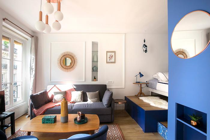 deco studio 20m2 avec canapé gris table basse bois fauteuils bleus tapis rouge et gris lit sur estrade mur d accent bleu