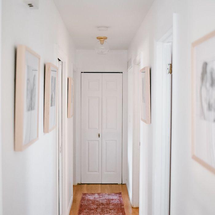 decoration couloir moderne avec des murs blancs parquet clair et deco de cadres avec photos en noir et blanc