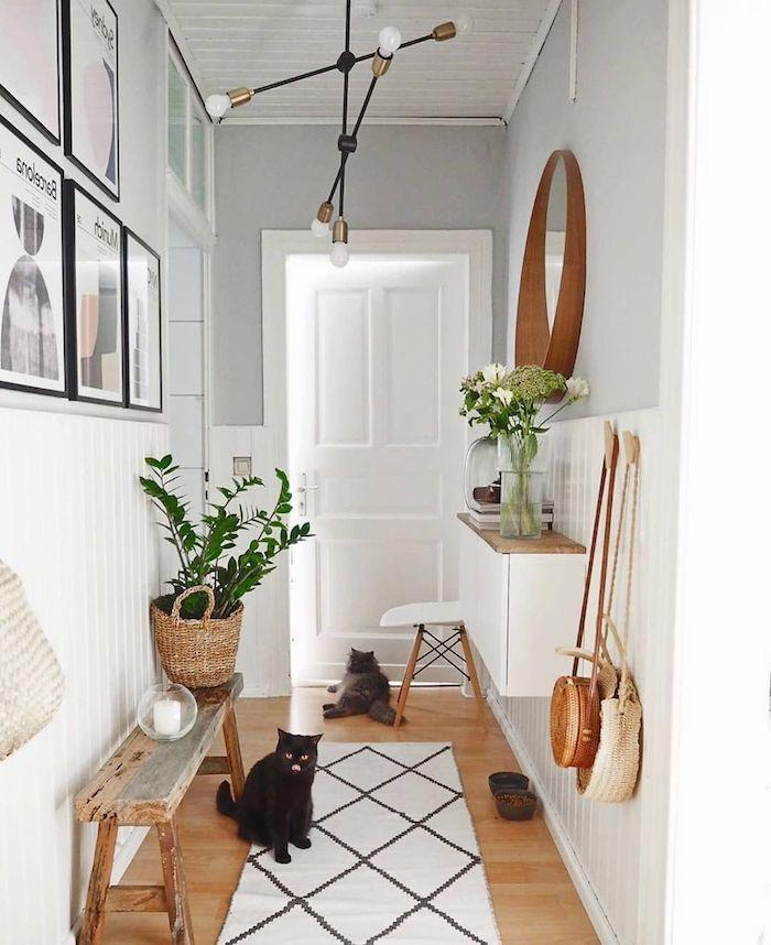 decoration couloir moderne repeint en blanc avec parquet bois clair tapis blanc geometrique banc entrée bois brut vases de fleurs lambris blanc