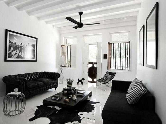 decoration mur interieur salon canapé noir plafond poutres bois apparentes ventilateur de plafond coussins rayures blanc et noir
