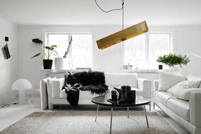 design interieur style minimaliste luminaire or canapé blanc plaid fausse fourrure noire plantes vertes d intérieur deco noir et blanc