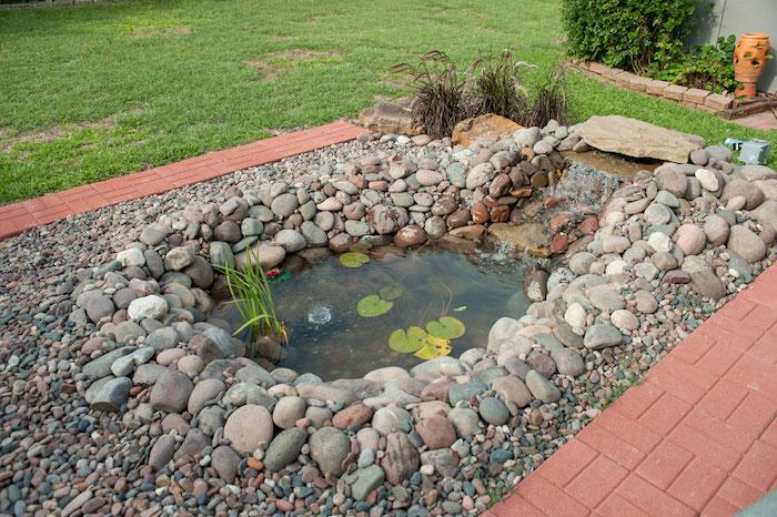 exemple de bassin d ornement peu profond entourée de pierres dans l arrière cour d une maison