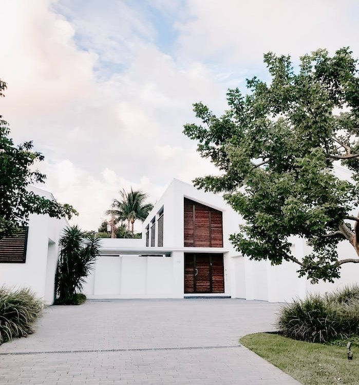 exemple de maison de lux exterieur couleur blanche et volets de bois avec des végétaux verts arbres exemple desing eco responsable d actialité
