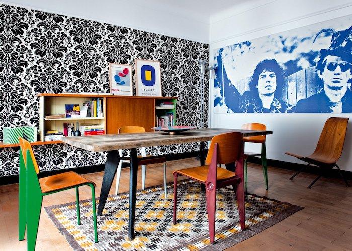 exemple de salle à manger style année 70 avec tapis coloré table bois et metal et chaises bois et metal mur papier peint noir et blanc fleuri deco ancienne
