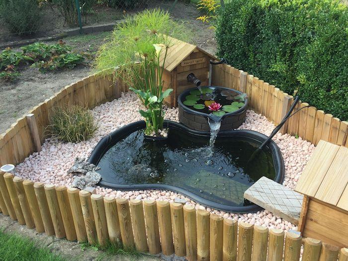 exemple installation de bassin préformé de couleur noire avec autre bassin à coté enterré dans sol en cailloux entourée de palissade bois