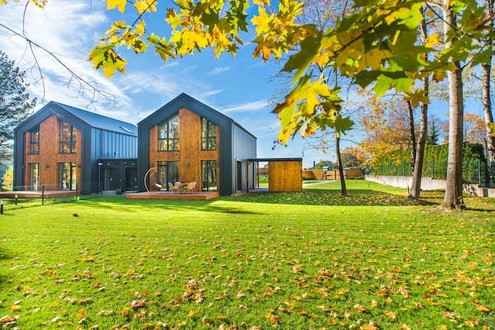 exemple maison eco friendly idée maison moderne bois ecologique au milieu d un gazon avec terrasse en bois équipée d un salon de jardin