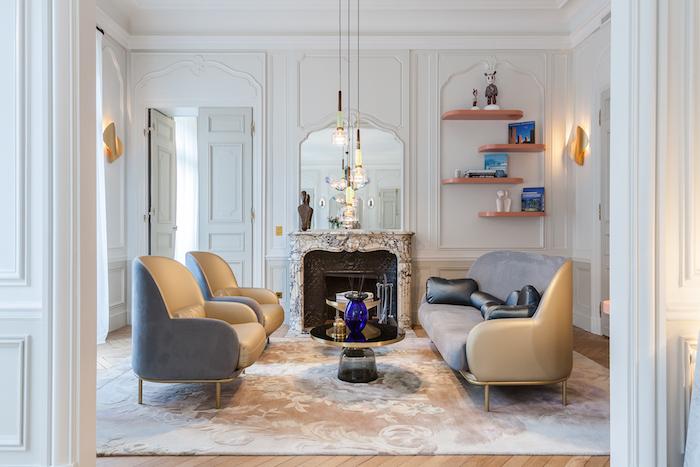 exmeple décoration salon appartement canapé et fauteuils gris tapis fleuri cheminée marbre murs décorés de moulures parquet bois clair