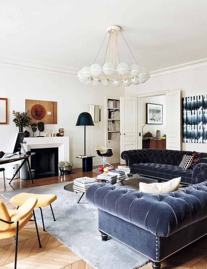 gros canapés capitonnés tapis gris clair chaise et repose pied jaune table basse design cheminée blanche moderne parquet clair murs blancs deco haussmannien