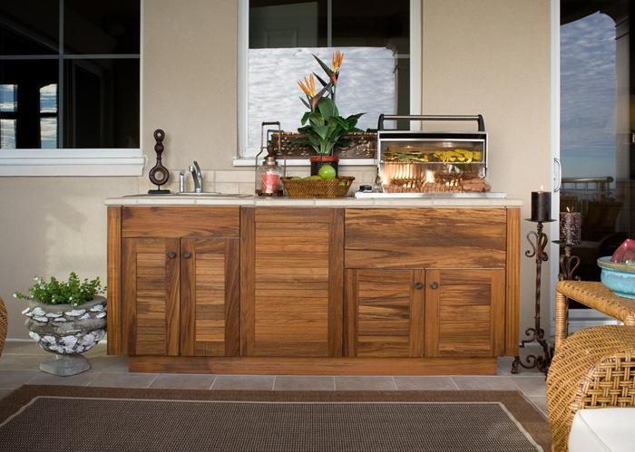idée comment installer une petite cuisine d ete extérieure avec meubles bas en bois foncé plan de travail aspect pierre naturelle