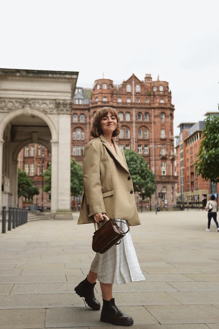 idée de style vestimentaire femme blazer oversize beige jupe blanche fluide bottines cuir noir sac à main cuir marron