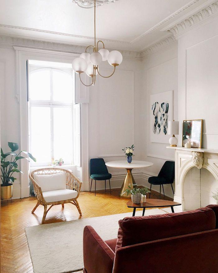 idée classique d appartement parisien avec parquet chevron chaise tressée canapé rouge tapis blanc coin table laiton et chaises vertes