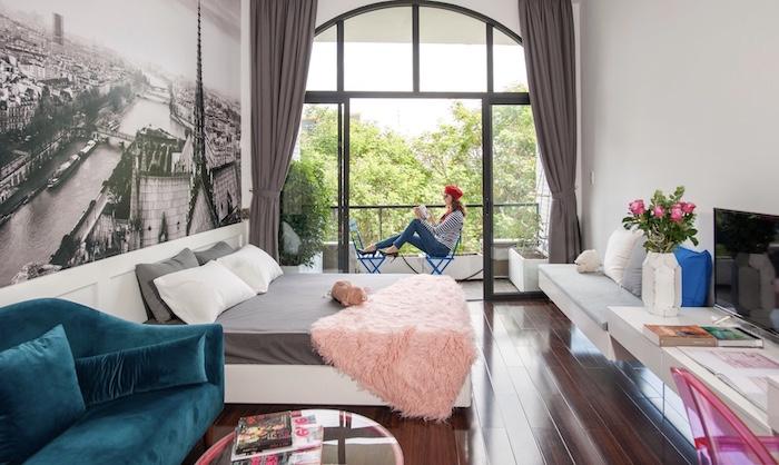 idée déco studio 20m2 avec lit gris et blanc plaid rose canapé bleu paon banc suspendu petit balcon pappier peint paysage photomural vue de paris