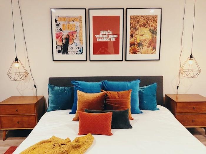 idée de coussins colorés sur in lit et plaid jaune moutard à grosses mailles deux meubles de nuit bois et suspensions laiton tableau deco murale affiches retro objet année 70