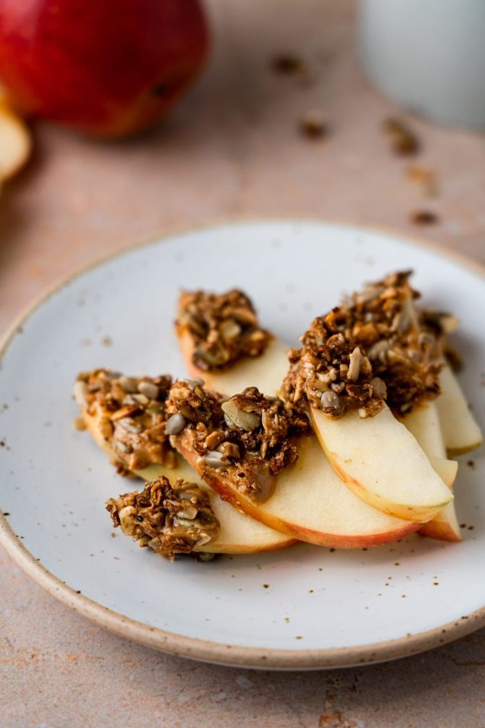 idée de tranches de pomme avec granola au beurre de cacahuete constitutée de graines flocons noix de coco et autres