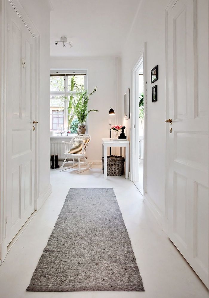idée deco couloir tout blanc avec des portes blanches et tapis gris meuble table entrée blanche chaise à bascule blanche decoration scandinave maison