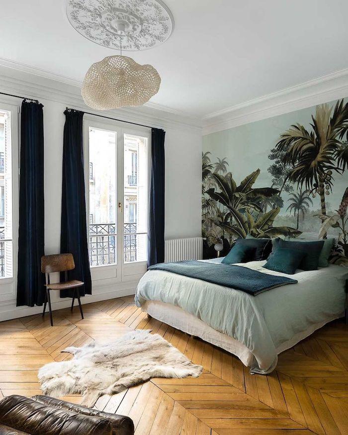 idée papier peint exotique en tete de lit ligne de lit blanc et vert parquet bois chevron rideaux bleus petit tapis fourrure grandes fenetres