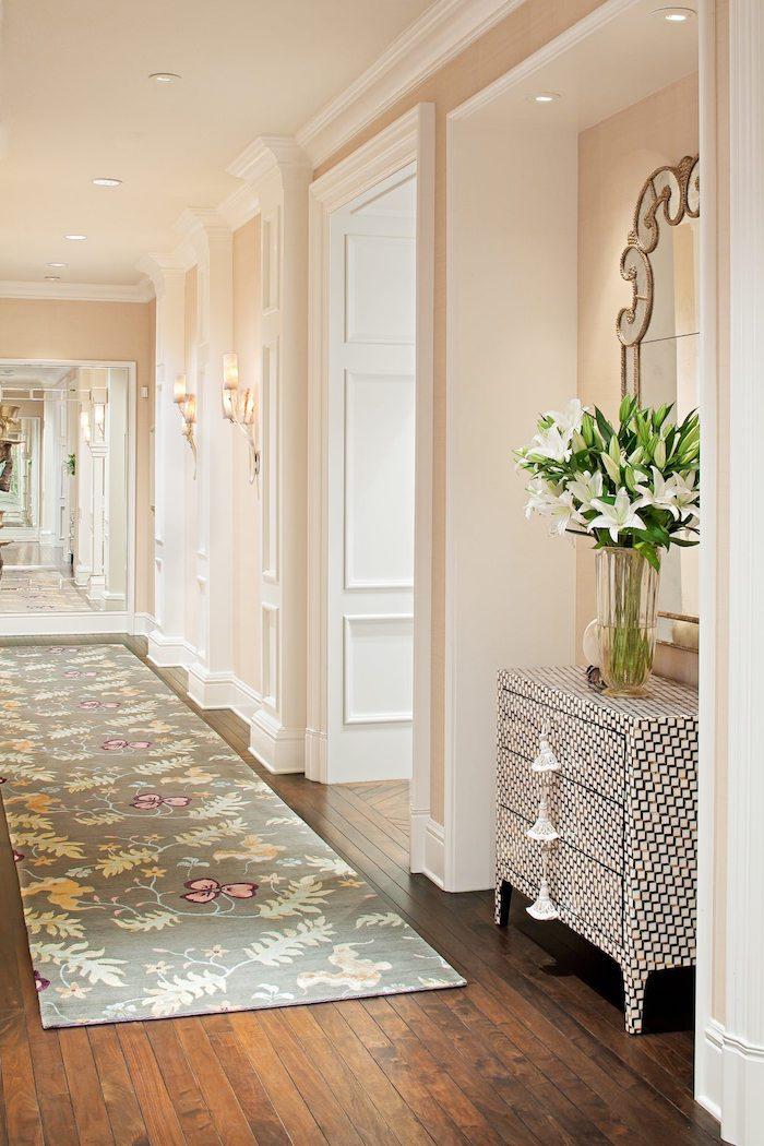 idée peinture couloir beige saumon avec des portes blanches parquet bois ancien tapis gris fleuri meuble couloir original