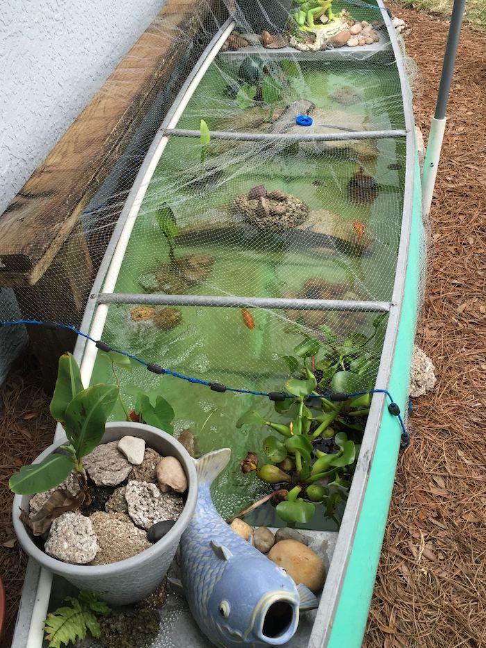 idee de bassin poisson exterieur dans un vieux bateau avec des plantes aquatiques et poissons avec figurines de poisson