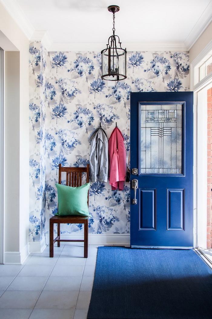 idee de papier peint pour couloir etroit et sombre avec tapis et porte bleu marine carrelage blanc et mur de fond papier peint fleuri