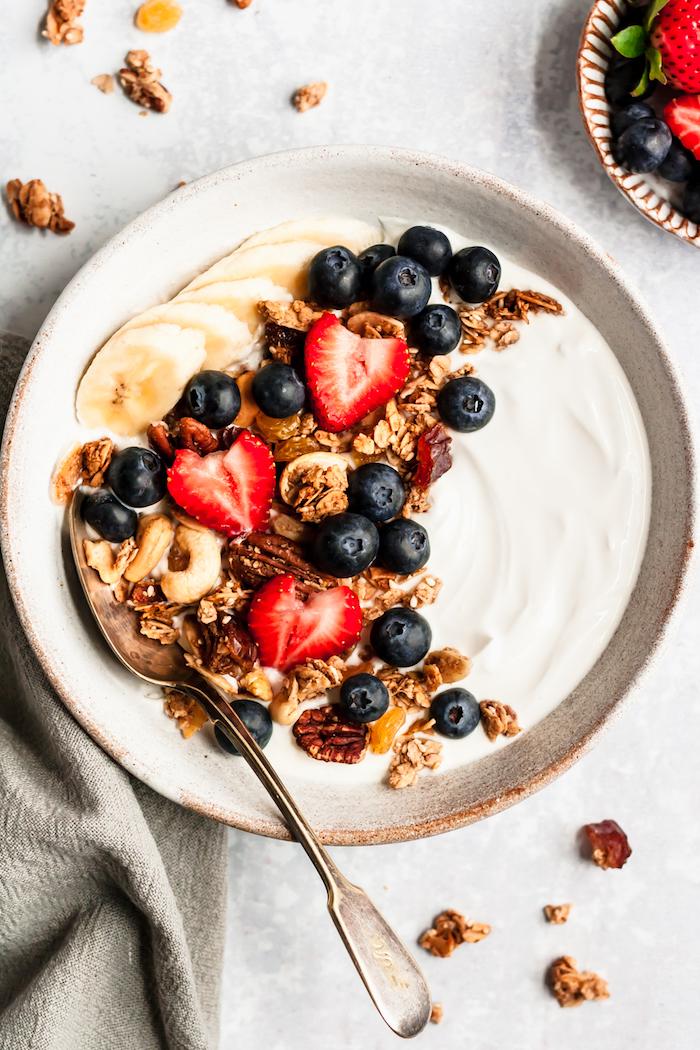 idee de petit dejeuner ideal museli maison vegan sans gluten à base de flocons d avoine raisins dattes graines variées et fruits rouges sur canapé de yaourt grec