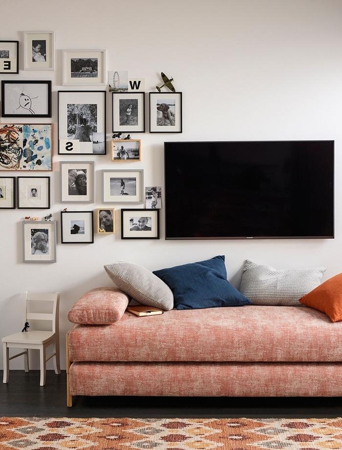 idee deco mur salon canapé corail tapis motifs géométriques en beige et marron cadres photos noirs photo blanc et noir