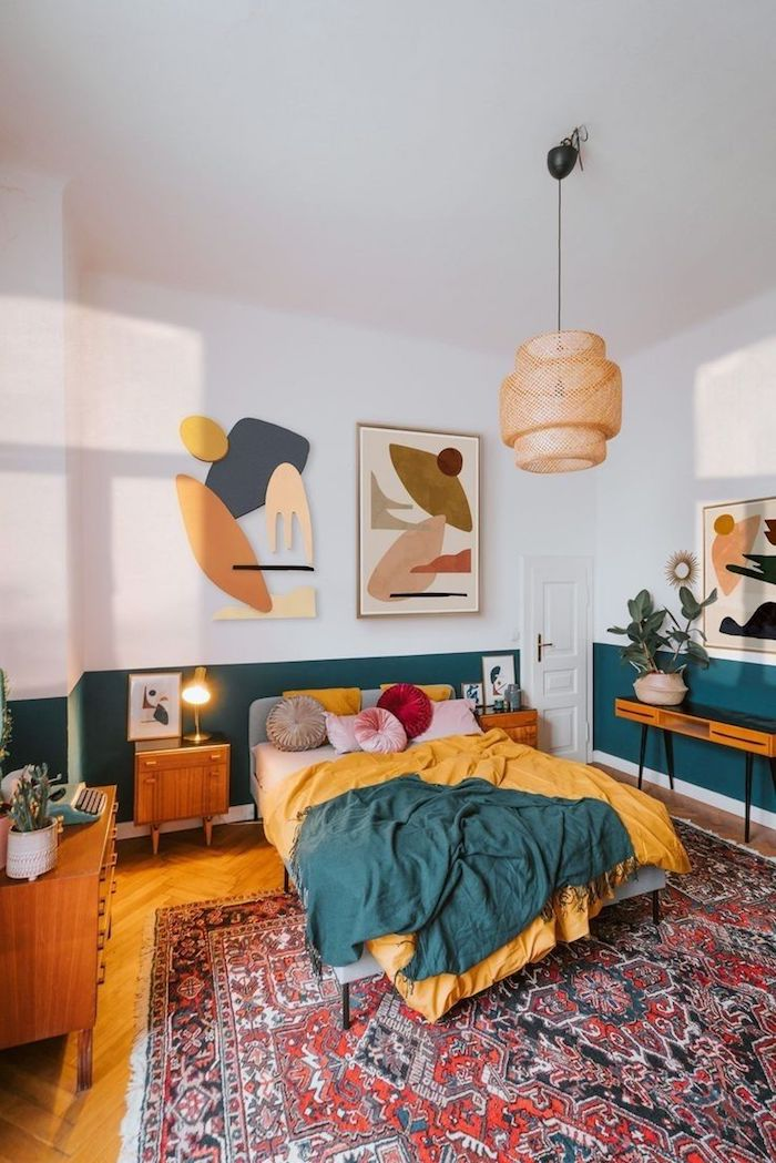 linge de lit jaune et bleu de vert sur parquet bois clair déoré de tapis coloré boheme soubassement peinture vert petrole deco murale psychadélique suspension eotique déco seventies colorée