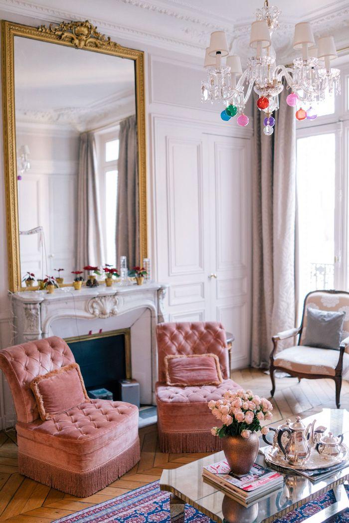 lustre à pampilles colorées fauteuils saumon capitonnés tapis oriental coloré table basse design fausse cheminée et miroir encadrement or décoration appartement moderne