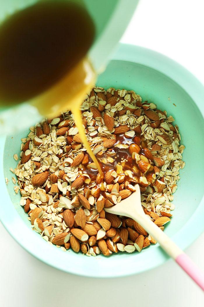 mélanger ingrédients secs et liquides dans un saladier mélange flocons d avoine amandes quinoa sirop d erable huile de coco