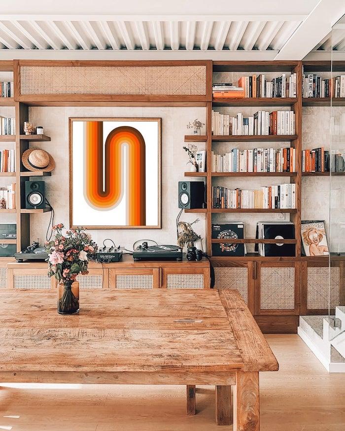 meuble cannage bas table bois brut et bouquet de fleurs en vase etagere surchargée de livre art tableau mural en lignes arrondies colorées