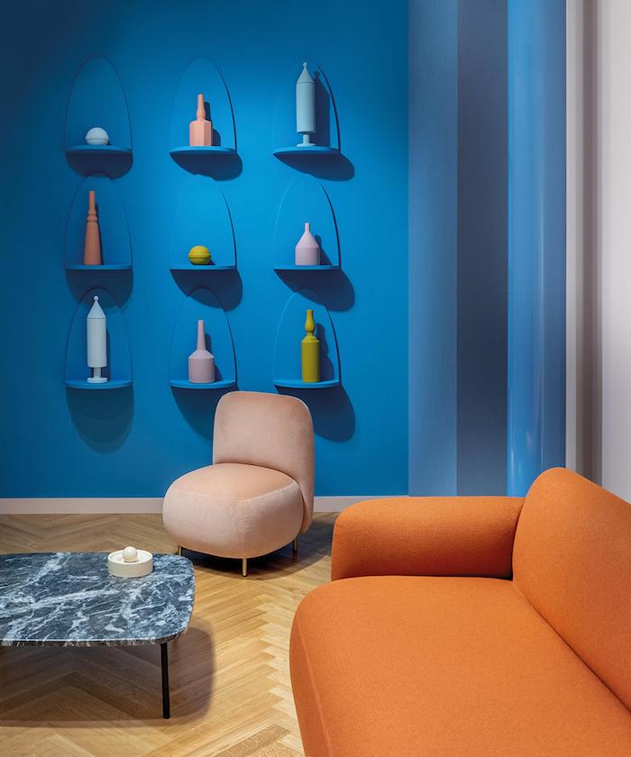 mobilier aux contours arrondis canapé orange et fauteuil beige table marbre gris mur bleu avec des vases arrondis meuble année 70
