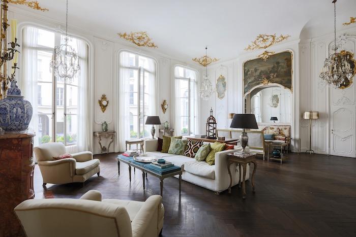 modele deco appartement haussmannien avec canapé et fauteuils blanc cassé table basse à coussins bleus parquet bois chevron murs blancs accent dorés