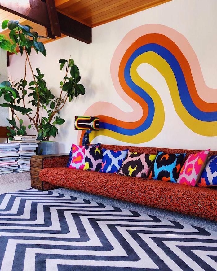 motif coloré mural deco psuchadélique deco salon vintage seventies avec canapé motif leopard coussins colorés plantes vertes et piles de magazines