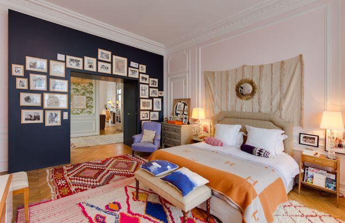 mur bleu marine lit à couverture rouge et beige tapis colorés tissage mural blanc cassé table de nuit bois commode original déco murale de cadres pghoo snoir et blanc