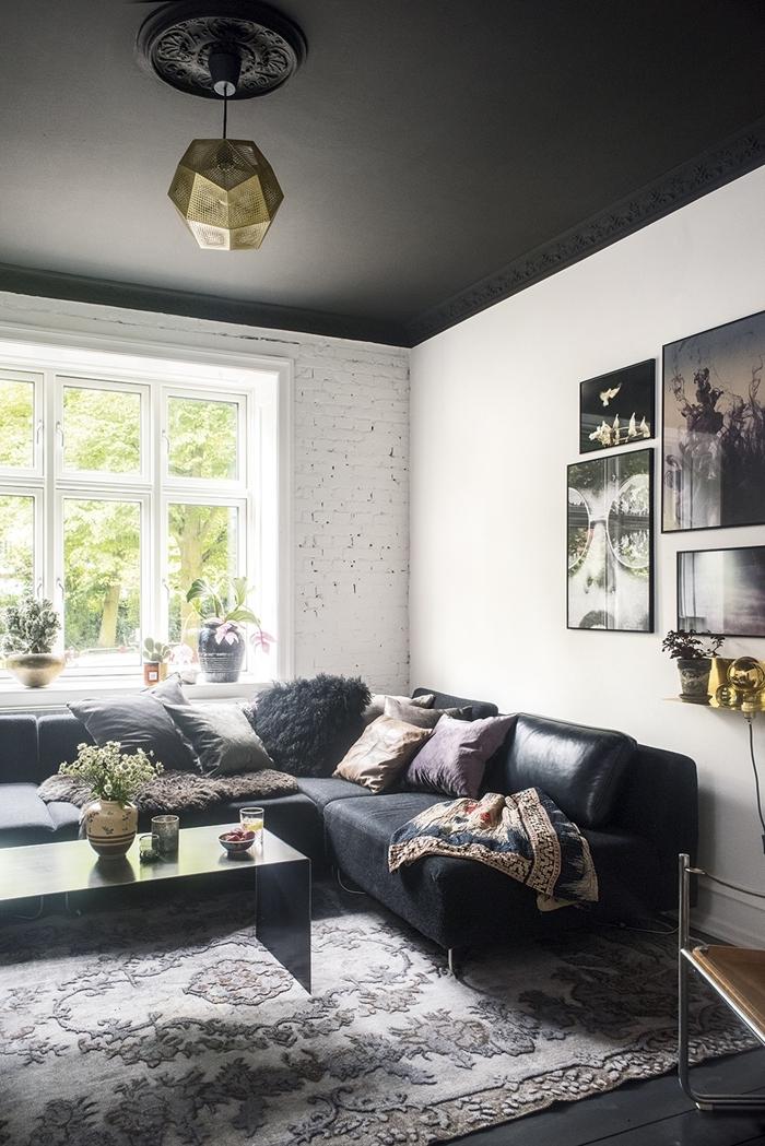 mur briques blanches plafond gris anthracite suspension luminaire or canapé d angle noir mat decoration salon design