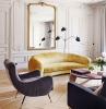 murs blancs décorés de volutes parquet bois clair chevron table basse bois et marbre fauteuil gris deco florale centre de table