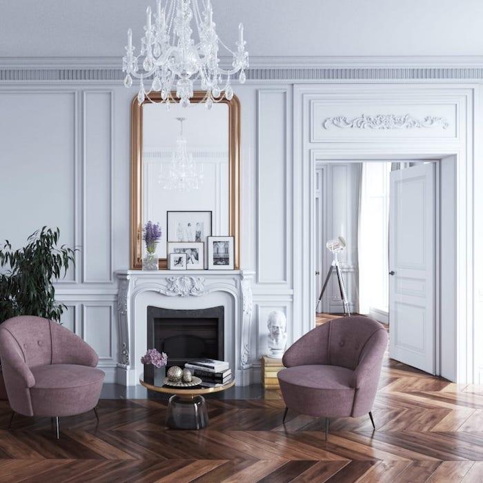 murs et cheminée couleur blanche fauteuils violets parquet bois foncé decoration de cadres noir et blanc
