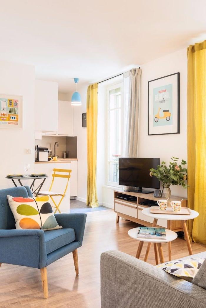 murs et cuisine blanche rideaux jaunes parquet bois clair fauteuil bleu de gris tables basses gigongnes meuble tv bois et blanc