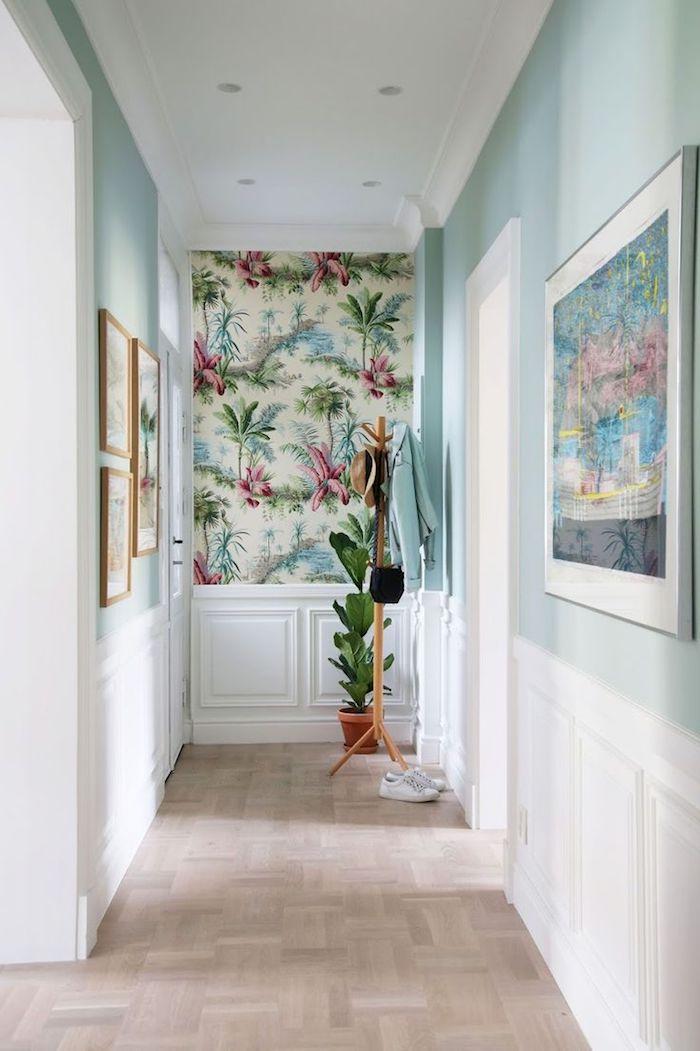 pan de mur décoré de papier peint tropical dans un couloir en blanc et bleu clair avec cadres decoratifs soubassement blanc idée déco couloiur lumineux