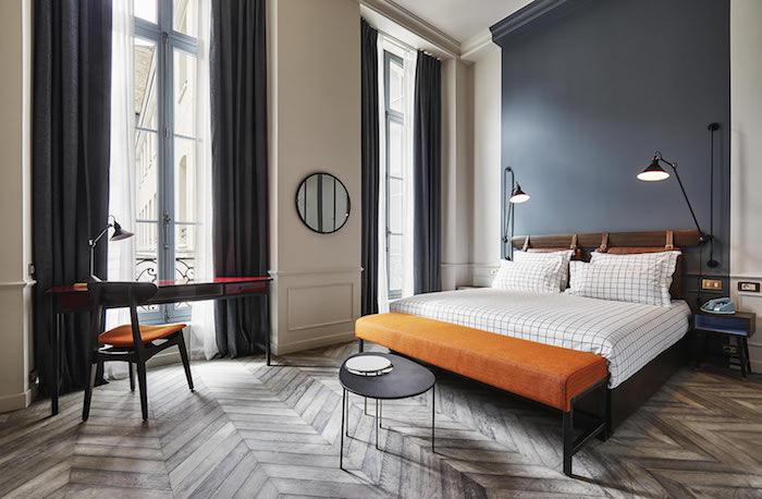 pan de mur gris lit bois et linge de lit à carreaux bout de lit orange coin bureau vintage rideaux grises idee interieur appartement industriel