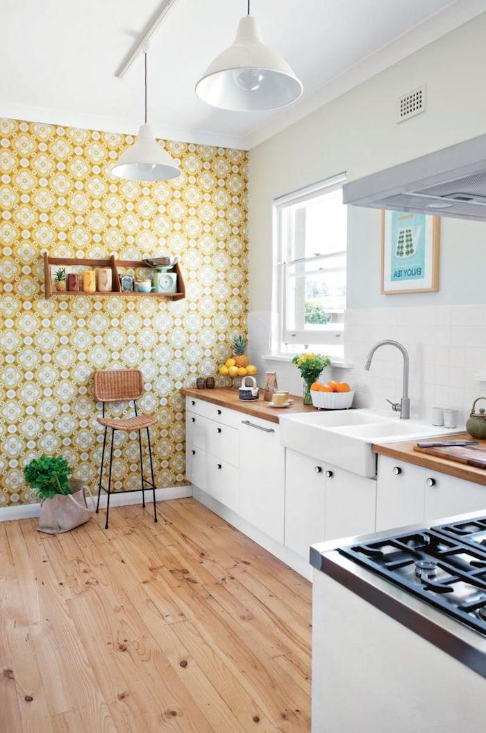 papier peint fleuri sur un mur meuble cuisine bas avec plan de travail bois étagère ouverte surchargée de vaisselle parquet bois clair