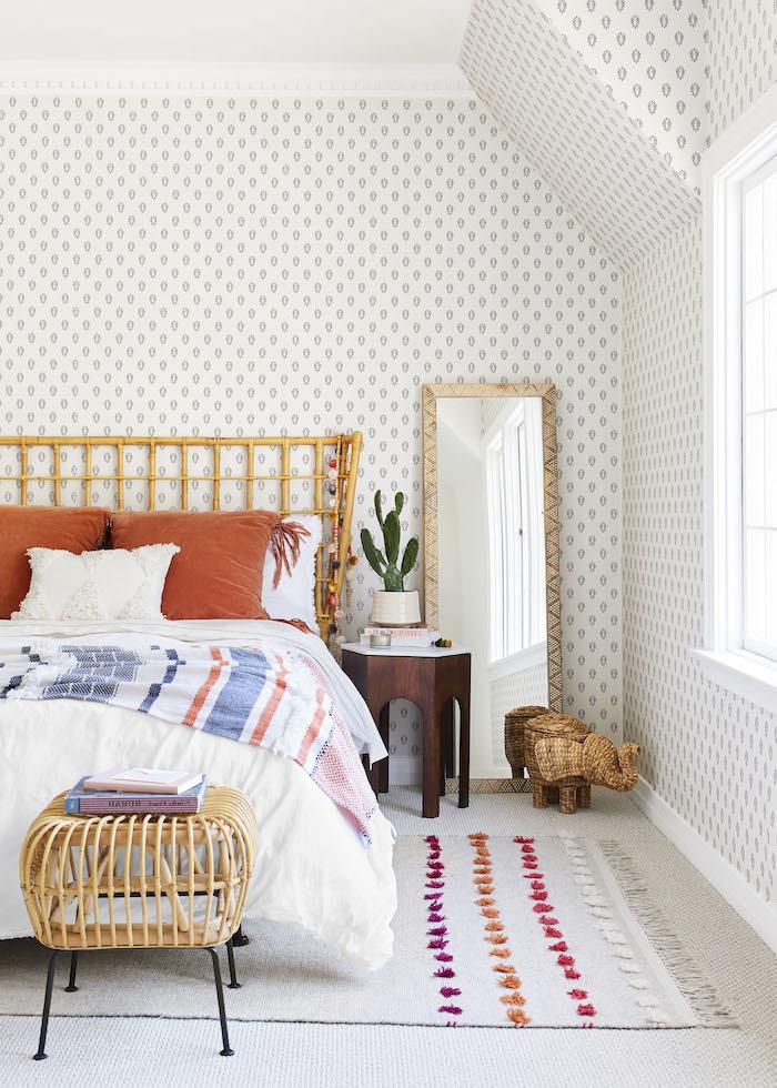 papier pent à motif gris floral tapis à pompons za franges coussins orange et couverture de lit à rayures sur linge d elit blanc table de nuit bois marron