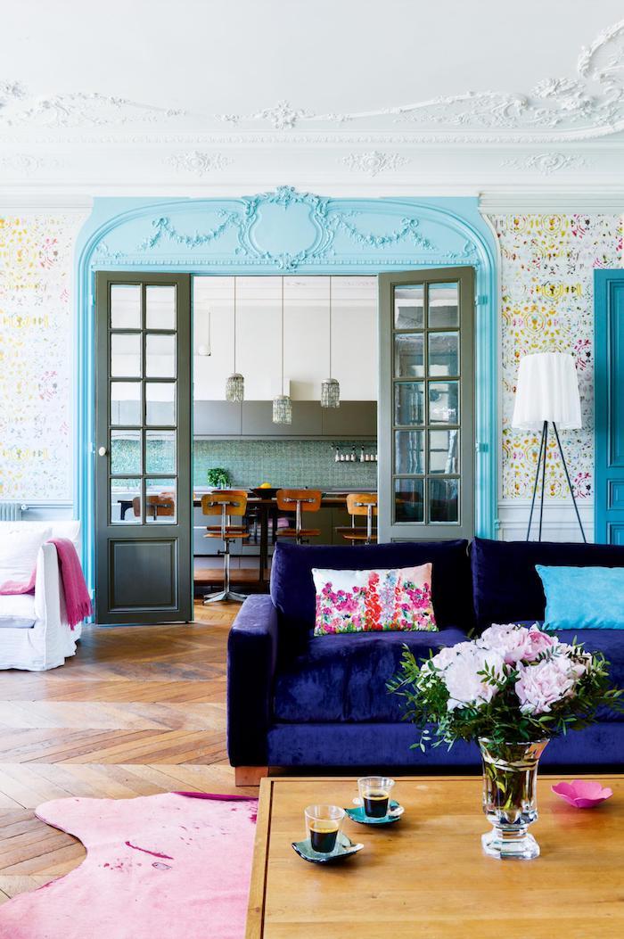 parquet chevron vrut canapé viole foncé table basse bois tapos rose ouverture sur cuisine bleu avec nbar et chaises hautes