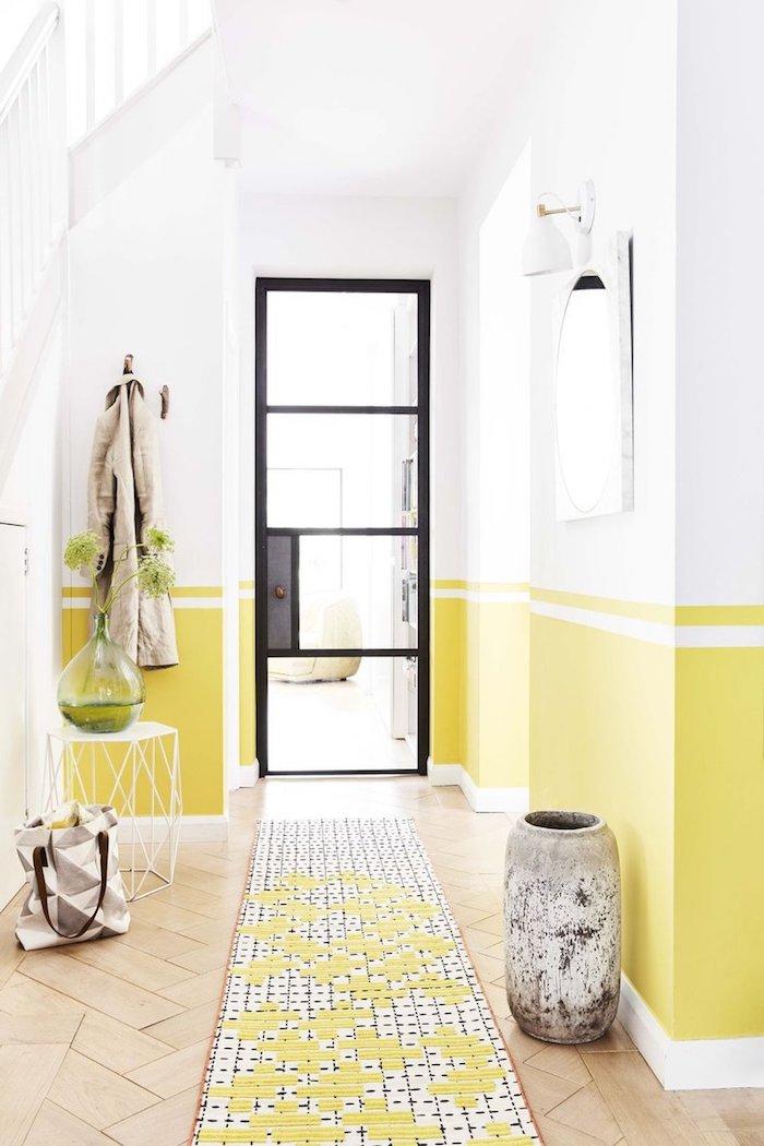 peindre couloir deux ccouleurs soubassement peinture jaune et murs blancs avec tapis noir et blanc et porte verrière noir et verre