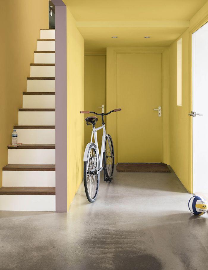 peinture couloir etroit repeint de jaune avec sol gris effet beton et escalier à pas de bois