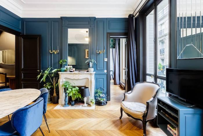 peinture murale bleu foncé parquet bois clair chevron cheminée blanche table marbre et chaises bleu marine décoration appartement moderne de luxe