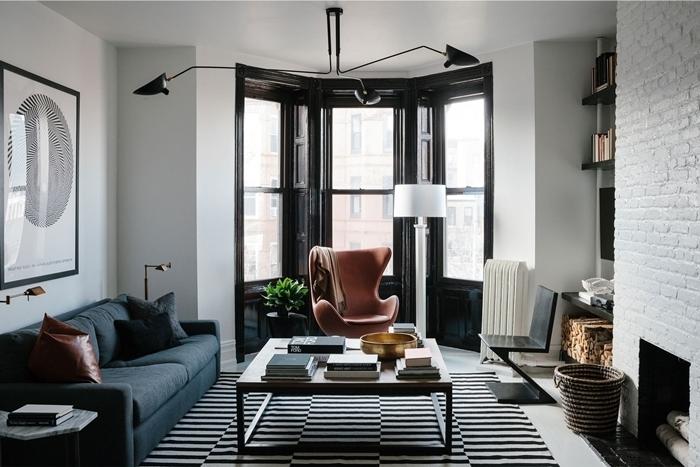 peinture noir et blanc salon mur briques blanches cheminée panier tressé tapis blanc et noir canapé bleu foncé lampe blanche