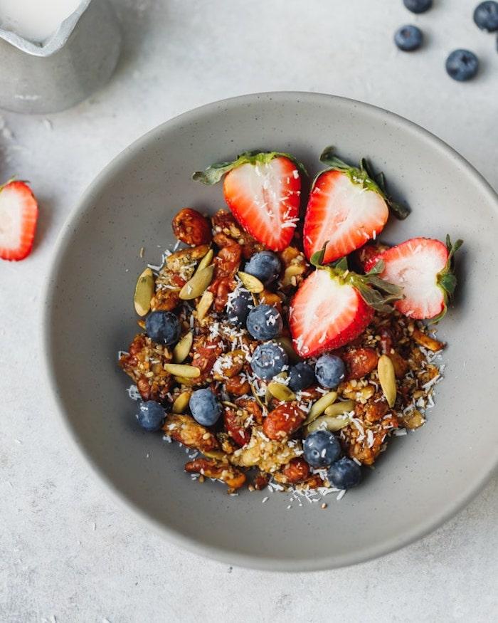 petit dejeuner ideal idee pour faire granola à base de noix graines variés à l huile de coco et édulcorant et topping de fruits rouges manger équilibré