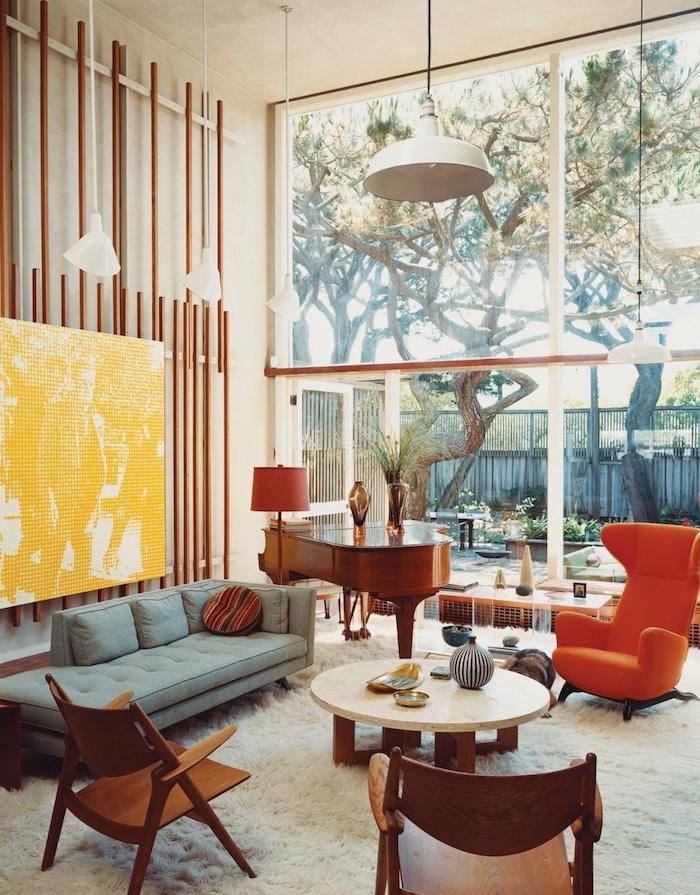 piano vintage de bois fauteuil oeuf orange canapé gris clair tapis blanc moelleux chaises bois et table basse bois et marbre tableau jaune enorme, déco années 70