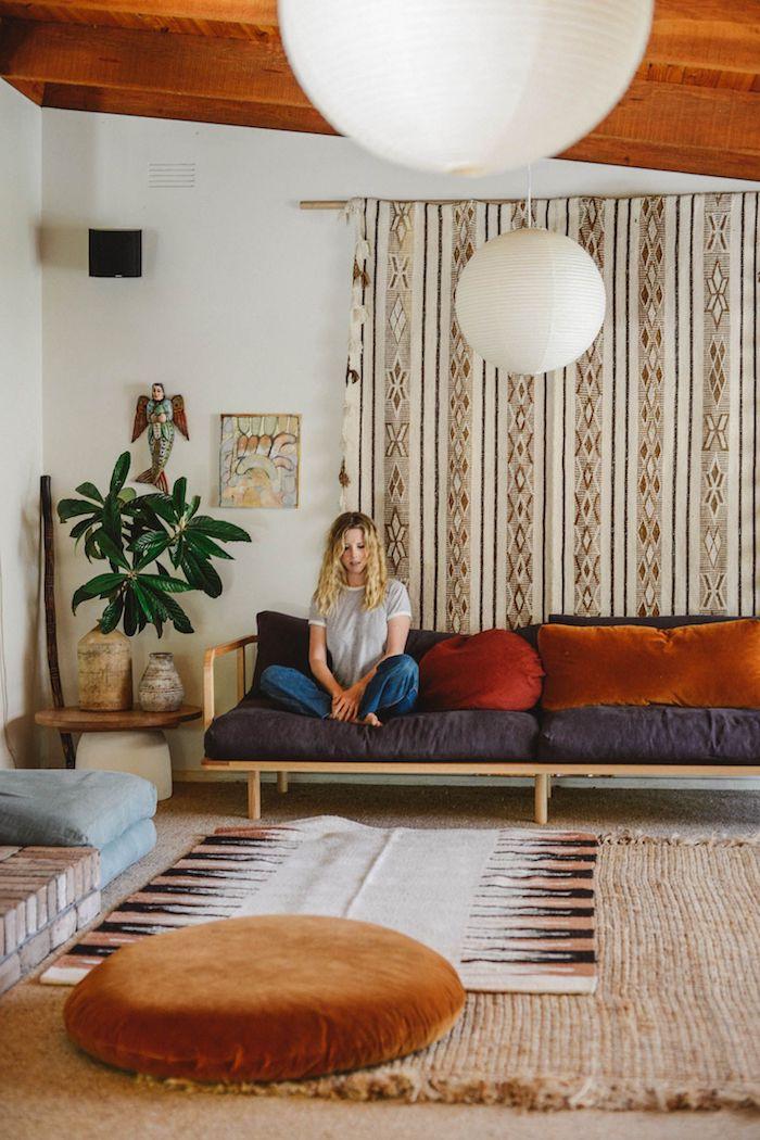 plafond de bois canapé boid avec coussin de dos et d assise gris anthracite et des coussins coloré pouf marron clair tapis beige plabte verte rideau voilage mural